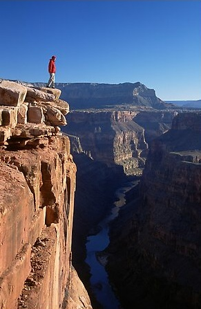 Man standing at edge of Grand Canyon at Toroweap, early morning. Grand Canyon National Park, Arizona, USA.